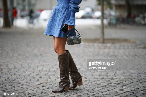 Fashion Week guest wearing a blue dress and Fendi boots and bag on August 08 2019 in Copenhagen Denmark