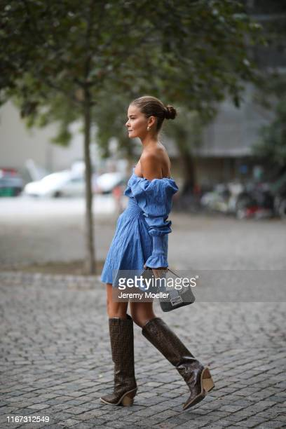 Fashion Week guest wearing a blue dress and Fendi boots and bag on August 08, 2019 in Copenhagen, Denmark.