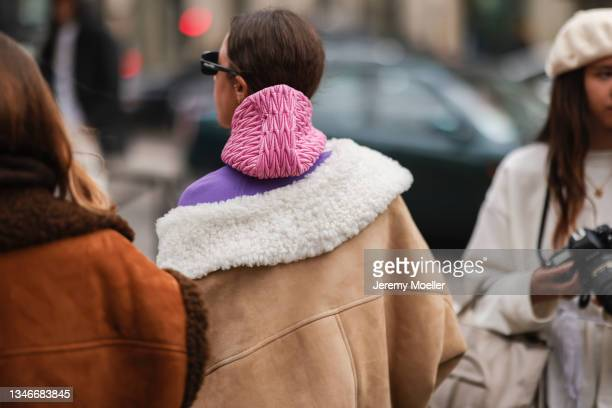 Fashion Week Guest wearing a brown jacket and a purple pullover outside Miu Miu Show on October 05, 2021 in Paris, France.