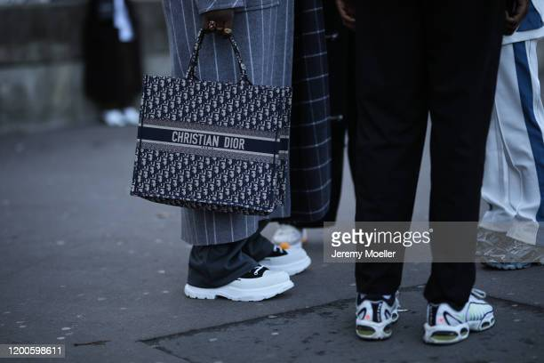 Fashion Week guest wearing a Dior travel bag before Les Benjamins on January 17, 2020 in Paris, France.