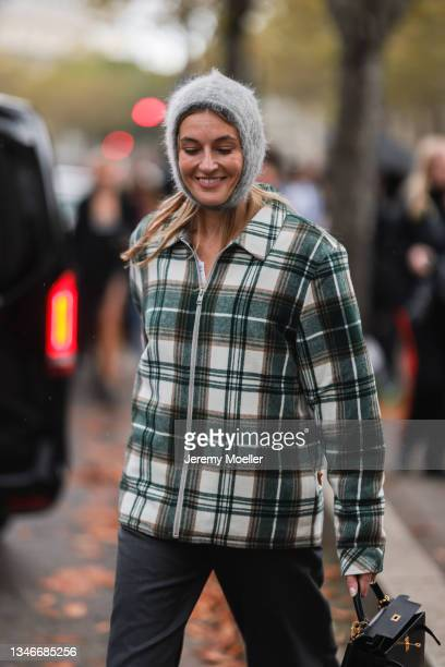 Fashion Week Guest wearing a green and white plaid jacket, a black trousers and a black bag outside Miu Miu Show on October 05, 2021 in Paris, France.