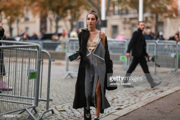 Fashion Week Guest wearing a grey dress with golden and silver details and a brown fur coat outside Miu Miu Show on October 05, 2021 in Paris, France.