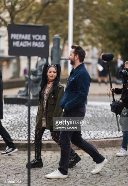 Fashion Week Guest wearing a olive jacket and black boots outside Miu Miu Show on October 05, 2021 in Paris, France.