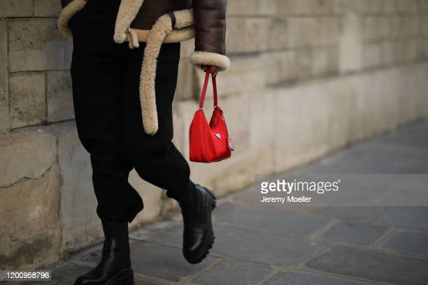 Fashion Week guest wearing a Prada Hobo bag in red and Bottega Veneta boots on January 20 2020 in Paris France