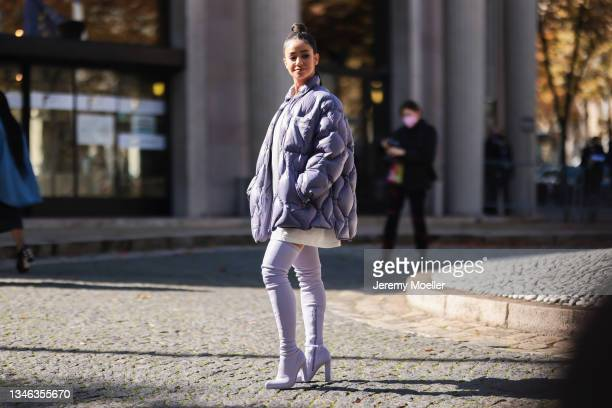 Fashion Week Guest wearing a purple jacket, boots and a white pullover outside Miu Miu Show on October 05, 2021 in Paris, France.