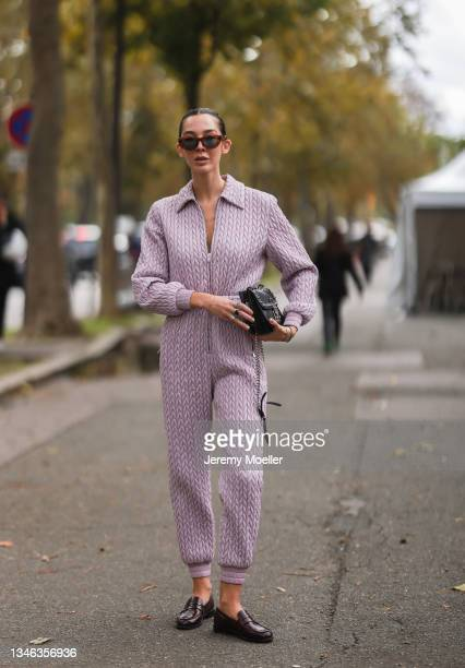 Fashion Week Guest wearing a purple suit and a black bag and sunglasses outside Miu Miu Show on October 05, 2021 in Paris, France.