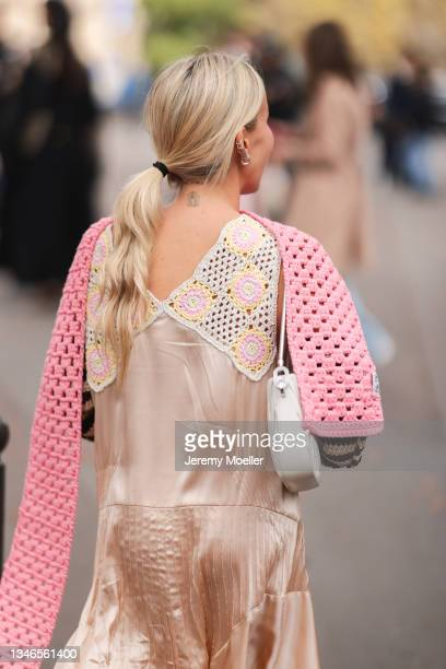 Fashion Week Guest wearing a rose dress with details and a pink scarf outside Miu Miu Show on October 05, 2021 in Paris, France.