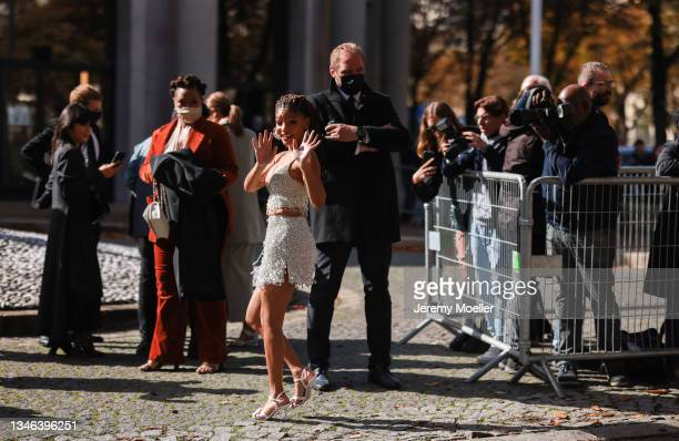 Fashion Week Guest wearing a shimmering dress and high heels outside Miu Miu Show on October 05, 2021 in Paris, France.