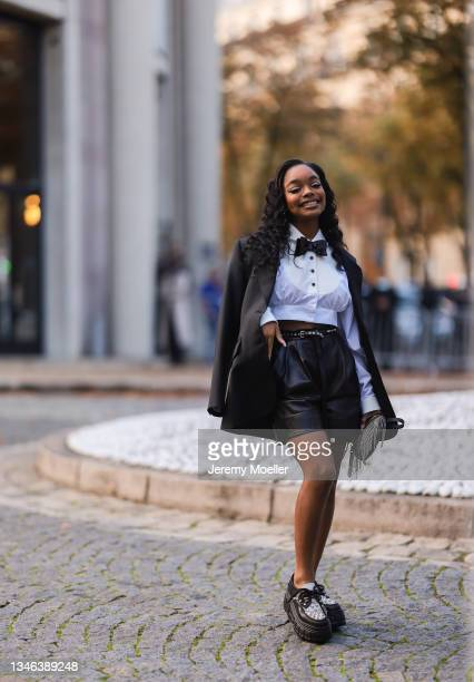 Fashion Week Guest wearing a white blouse, black leather pants and blazer and black and white shoes outside Miu Miu Show on October 05, 2021 in...