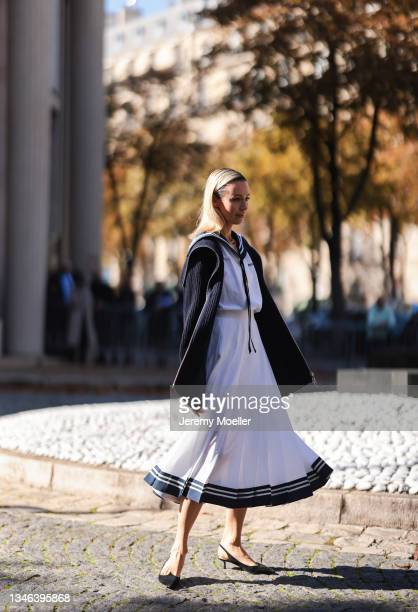Fashion Week Guest wearing a white dress and a black cardigan and black heels outside Miu Miu Show on October 05, 2021 in Paris, France.