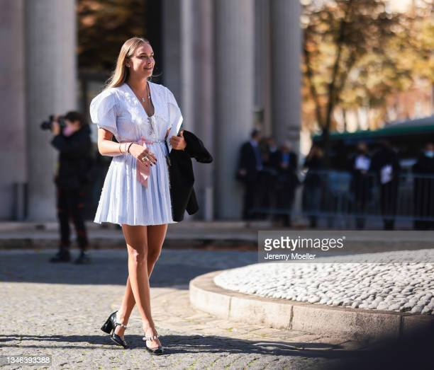 Fashion Week Guest wearing a white dress and black heels outside Miu Miu Show on October 05, 2021 in Paris, France.
