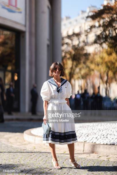 Fashion Week Guest wearing a white dress, white high heels, a blue bag and sunglasses outside Miu Miu Show on October 05, 2021 in Paris, France.