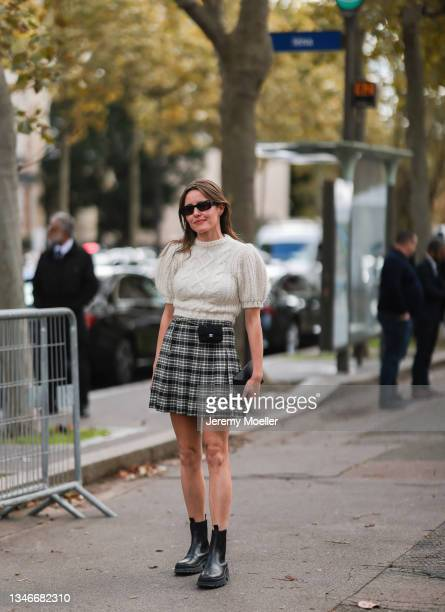 Fashion Week Guest wearing a white shirt and a black and white skirt with black boots outside Miu Miu Show on October 05, 2021 in Paris, France.