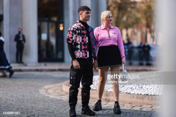 Fashion Week Guests wearing a pink pullover and a black skirt, a pink, white colored shirt and black pants outside Miu Miu Show on October 05, 2021...