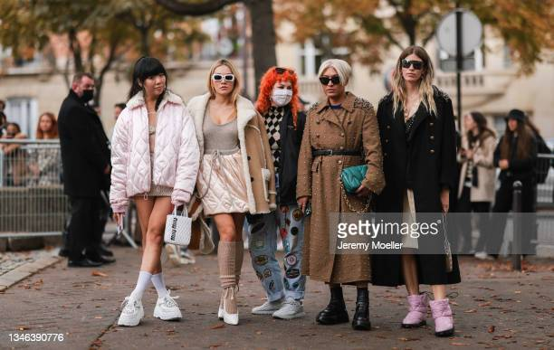 Fashion Week Guests wearing a rose jacket with white socks and sneakers, a brown fur jacket with a beige top and rose skirt and heels, a black blazer...
