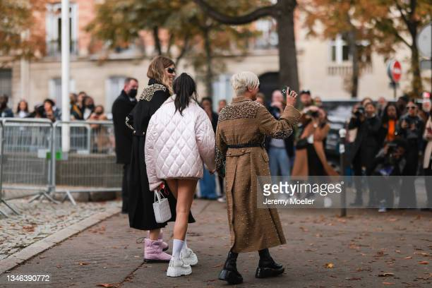 Fashion Week Guests wearing a rose jacket with white socks and sneakers and a long black coat with pink boots outside Miu Miu Show on October 05,...