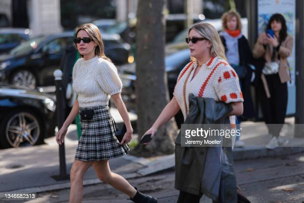 Fashion Week Guests wearing a white shirt and a black and white skirt with black boots and a orange white shirt and sunglasses outside Miu Miu Show...
