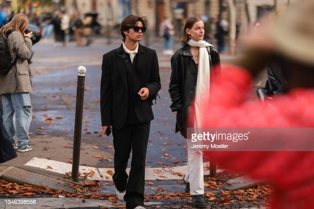 Fashion Week Guests wearing black blazer and black pants, and a white scarf outside Miu Miu Show on October 05, 2021 in Paris, France.