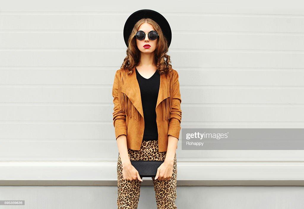 Fashion woman wearing elegant hat, jacket handbag clutch over background : Stock Photo