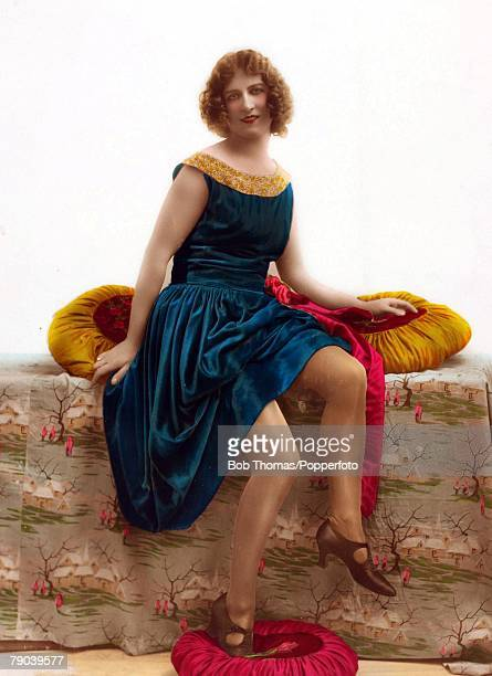 Fashion Woman with curled hair wearing a blue velvet dress with gold collar in a formal studio photograph circa 1920