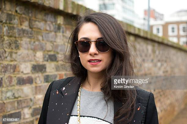 Fashion writer Amy Marietta wears a Mua Mua Dolls top Cres e Dim Coat and Tom Ford sunglasses on day 4 of London Collections Women on February 17...