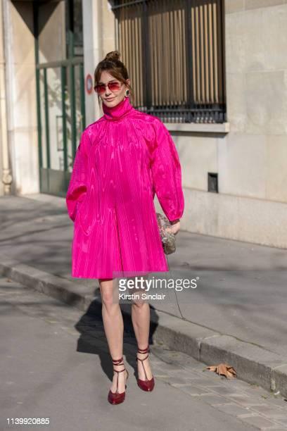 Fashion writer Ece Sukan wears a Nackiya dress Ninon earrings vintage sunglasses and Celine shoes on February 26 2019 in Paris France