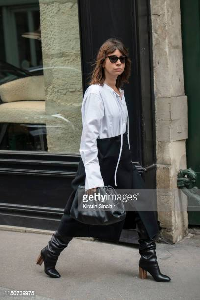 Fashion writer Natasha Golenberg wears black leather knee high boots and a black leather clutch bag, black mid length skirt and a white shirt on...