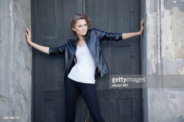 Fashion young woman with disarming glance closing door enter
