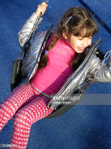 fashionable 5 years old girl sitting on swing. - 4 5 years stock pictures, royalty-free photos & images