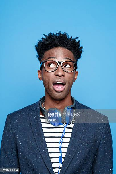 fashionable afro american young man against blue background - pulling funny faces stock pictures, royalty-free photos & images