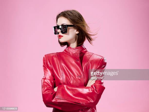 fashionable and cool woman crossed her arms over her chest and the wind blows her hair. - fashion stock pictures, royalty-free photos & images
