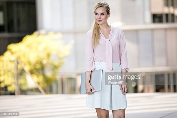 Fashionable blond businesswoman with laptop