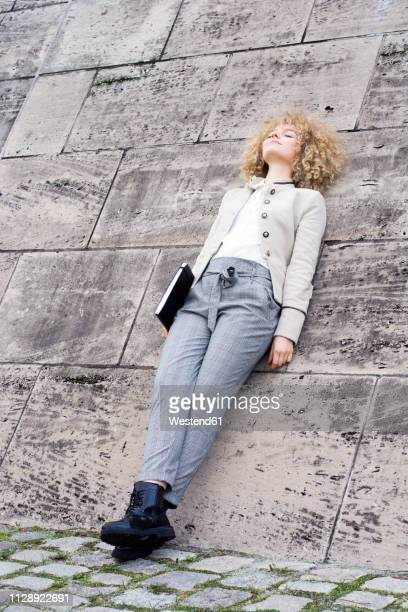 fashionable blond woman with folder leaning against wall having a rest - pause machen stock-fotos und bilder