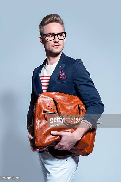 Fashionable blonde young man holding bag
