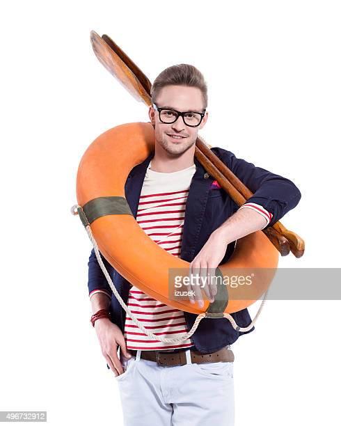 mode blonde jeune homme tenant rames croisées et lifebuoy - marin photos et images de collection