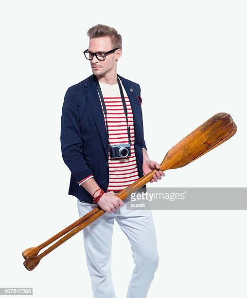 fashionable blonde young man holding oars - matroos stockfoto's en -beelden