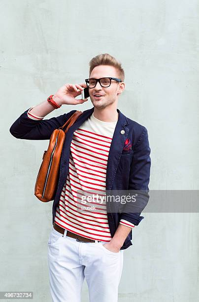 Fashionable blonde young man talking on cell phone