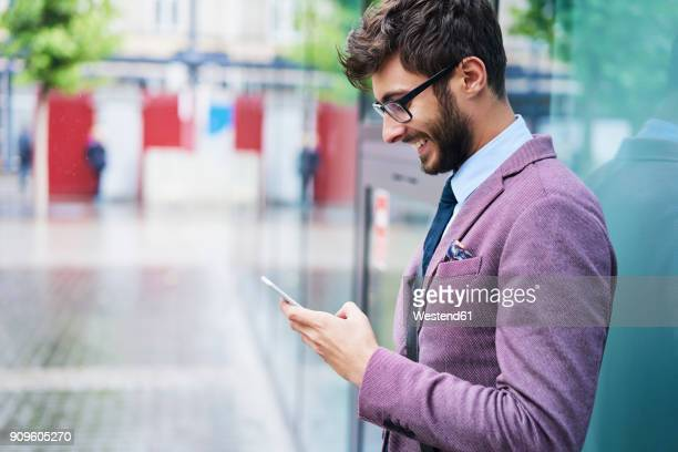 Fashionable businessman checking his cell phone
