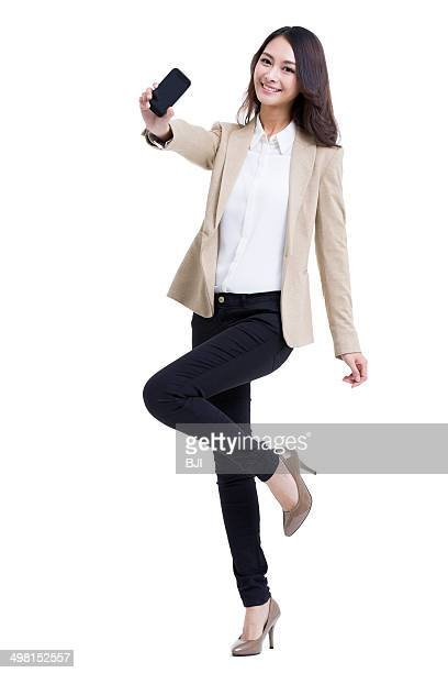 Fashionable businesswoman showing mobile phone