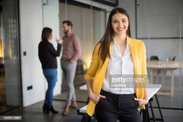 fashionabla affärskvinna står och tittar på kameran - gul bildbanksfoton och bilder