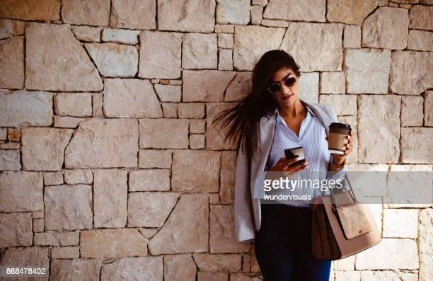 ar livre de mensagens de texto no celular e beber café elegante empresária - blazer - fotografias e filmes do acervo