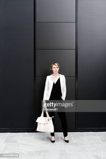 fashionable businesswoman wearing black and white clothes - hands in pockets stock pictures, royalty-free photos & images