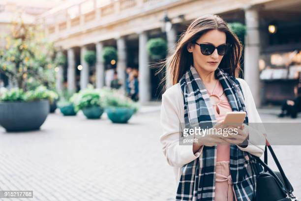 Fashionable city woman texting on the street