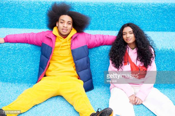 fashionable couple sitting on blue floor - generation z stock pictures, royalty-free photos & images