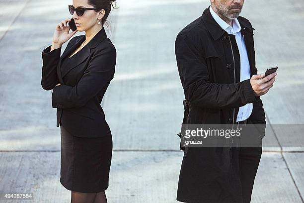 Fashionable couple using mobile phones outdoor.
