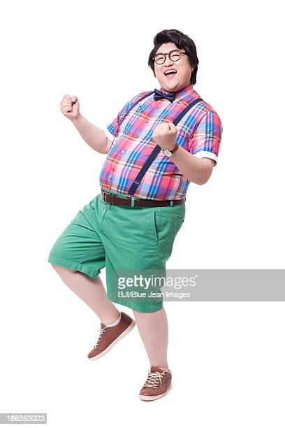 fashionable fat man celebrating with excitement - サスペンダー ストックフォトと画像