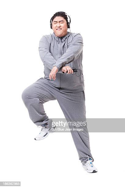 fashionable fat man listening to music and dancing - tracksuit bottoms stock pictures, royalty-free photos & images