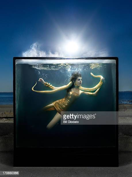 fashionable female in water tank with snake
