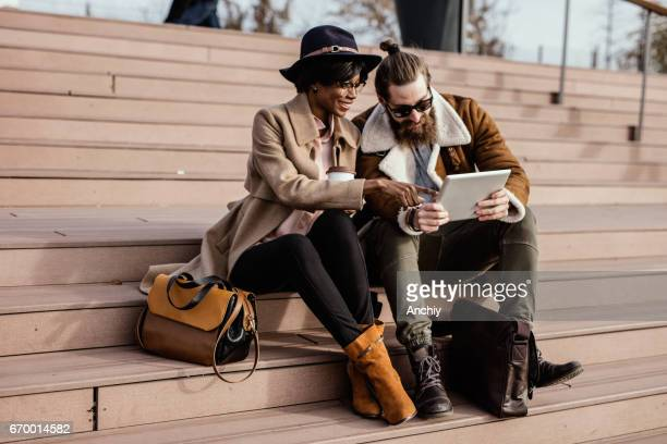 Fashionable friends sit on the stairway watch funny videos on a portable gadget