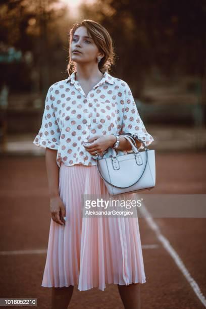 日没時にテニスコートに立っているファッショナブルな女の子
